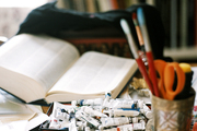 Art supplies, books, and fabric samples on a wooden table