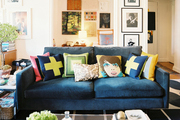 A blue couch covered in throw pillows atop a patterned rug