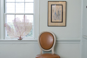 A Regency chair and elegant framed art in a calm Hamptons dining room