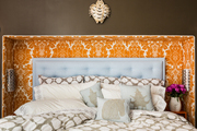 Against a colorful print, a bed dressed in a neutral palette