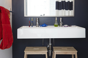 A floating white sink in the kids' bathroom is made accessible by two IKEA step stools.