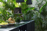 An outdoor kitchen with hanging woven string lights.