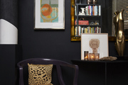 Small chair and abstract decor in front of rich dark walls.