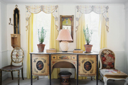A pair of potted plants on a sideboard backed by yellow curtains