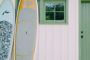 Surfboards leaning against a guest house.
