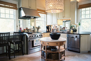 A travertine-topped circular island in a kitchen