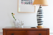 A wooden dresser topped with a painterly lamp and cactus-motif vases