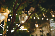 A string of tea lights and votives hang in the tress over an outdoor dinner party