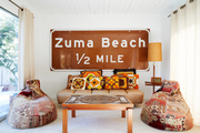 A Zuma Beach highway sign hung up in a living area.