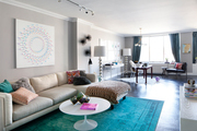 Low white couch with colorful throw pillows atop a bright accent rug in this multi-use room.