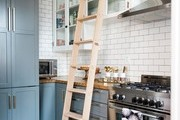 A contemporary kitchen with white subway tile and a ladder.