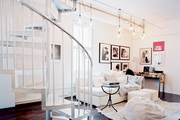 A spiral staircase in a living space filled with art and white furniture