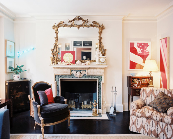 An antique gold mirror above a marble mantel surrounded by contemporary art