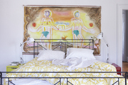 A painting of Adam and Eve over an unmade bed