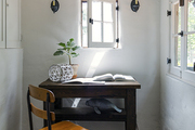 Small wooden desk in window lit room.