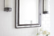 Tall framed mirror and wall-mounted lighting above a marble sink.