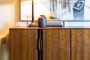 A midcentury wood console and table lamp against a painting