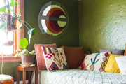 This room is decorated in 1970s style with olive green walls, a shag rug, and crochet textiles.