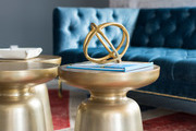 Matching gold pedestals in front of blue sofa.