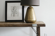 Framed art and lamp atop wooden table.