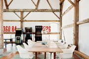A dining space in a barn with molded-plastic chairs and an arc lamp
