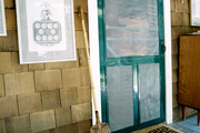 A Greek-key doormat paired with a green screen door on a shingled home