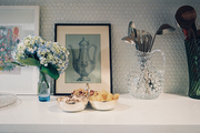 White countertops decorated with art and serving pieces against a penny-tile backsplash