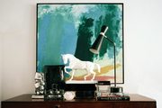 A white horse statue, a black task lamp, and decorative accessories on a wooden console