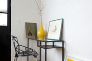 A modern desk area with a yellow vase and artwork on it.