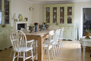 A long wood dining room table with assorted wooden chairs, potted roses and bulbs, a two wooden and glass storage hutches.