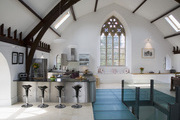 A minimalist gothic style building with high ceilings and a modern kitchen set up.