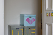 "This storage closet is made brighter with colorful graphic boxes that say ""Love Home""."
