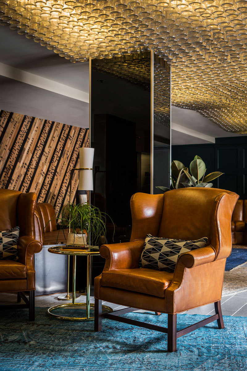 ELA Lighting created a custom lighting installation in the lobby, made with recycled whiskey bottles and designed by the team at Nicole Hollis.