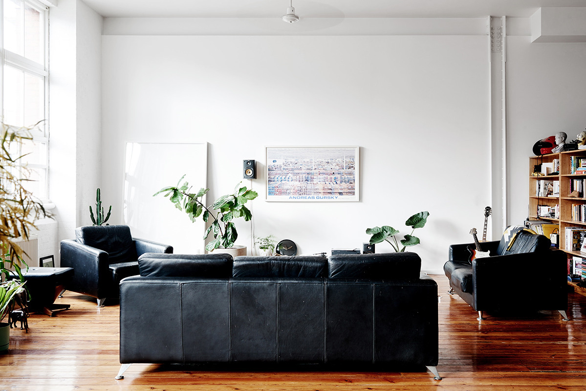 Laid-back black seating is balanced by delicate plants and a statement-making art print by Andreas Gursky.