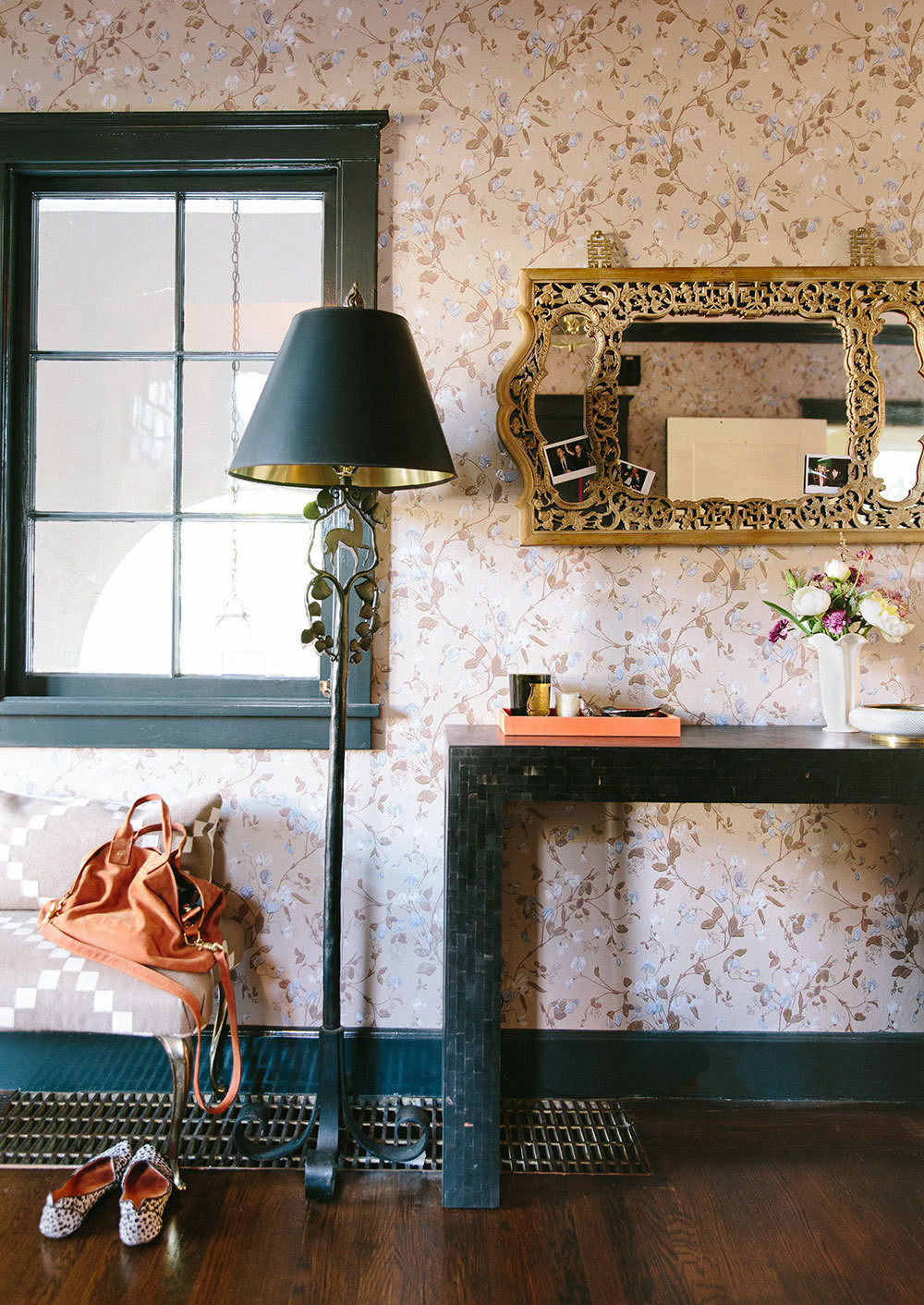 A bronze floor lamp and black console ground the botanical wallpaper in the entry.