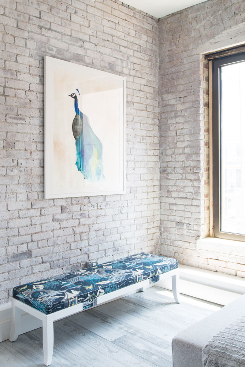 A peacock illustration by Christine Lindstrom hangs above a bench from One Kings Lane in complementary tones.