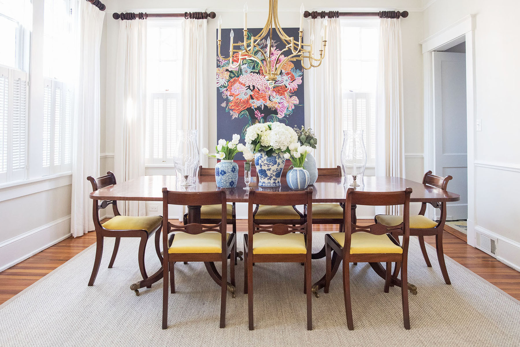 The couple host an annual disco brunch for their friends, in their extravagant dining room. Wayfair Rug | Scott Antique Markets Dining Table | Ballard Dining Chairs | Custom Drapes | The Menagerie Candle Shades.