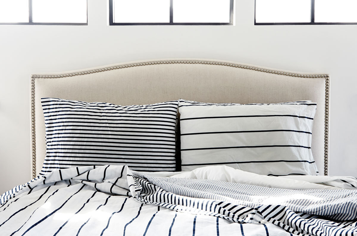 Striped linens are a crisp counterpoint to the upholstered headboard in the master bedroom.