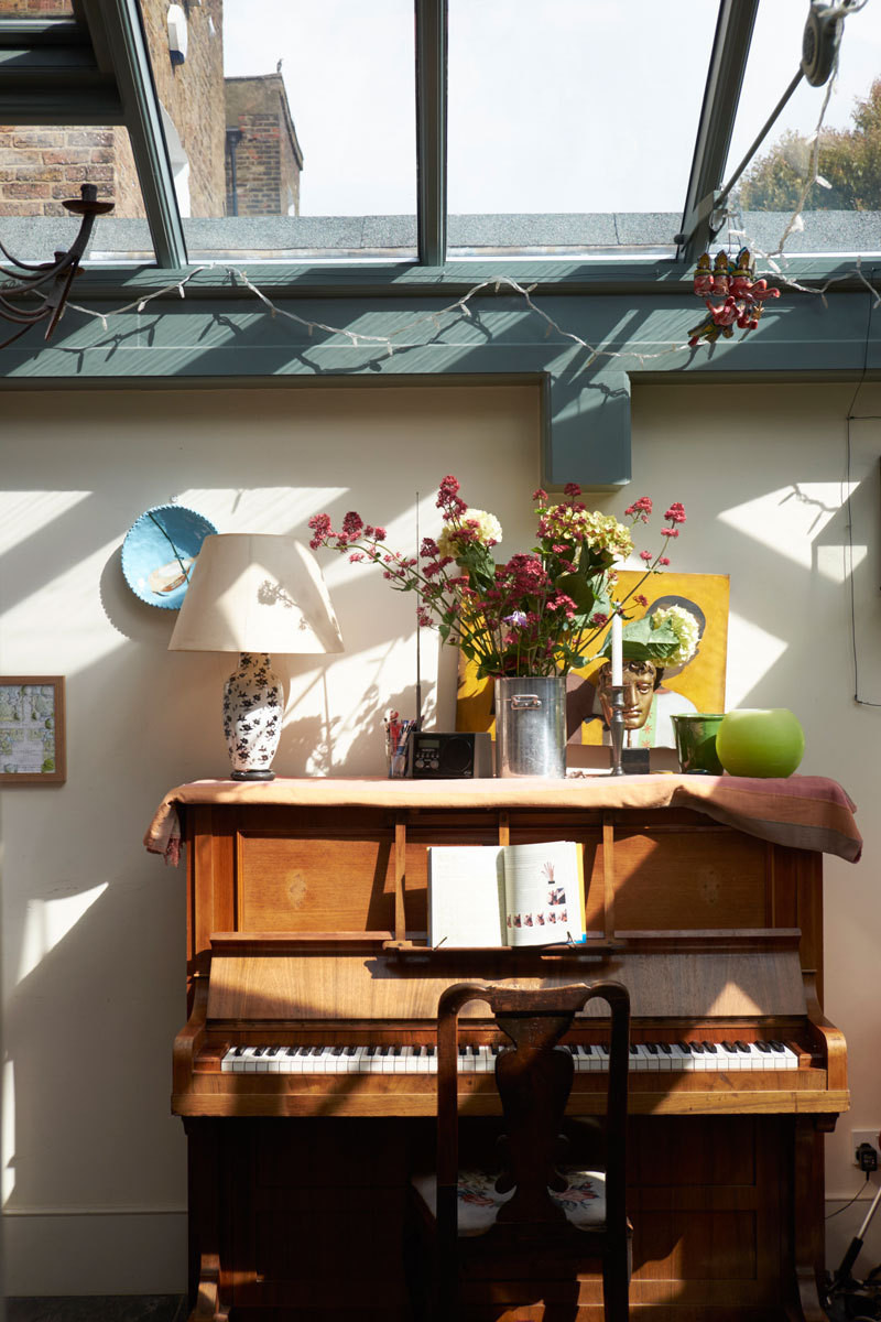 An antique piano stands next to the dining table in the atrium.