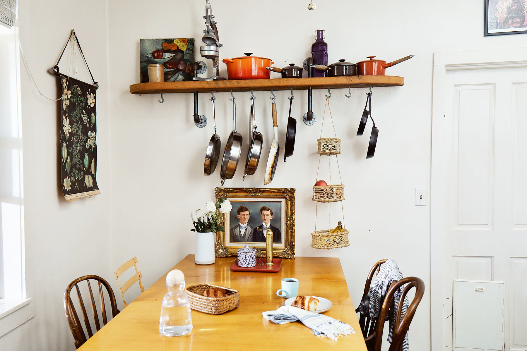 Rachel Colla's vintage cottage-style kitchen is decorated with repurposed family treasures.Vintage George Nelson for Herman Miller Dining Table | Vintage Bentwood Chairs | Vintage Artwork | Vintage Pots and Pans | Vintage Tapestry |Heath Mug |Heath Ceramics |Clad Home Water Pitcher |Atomic Garden Hanging Baskets.