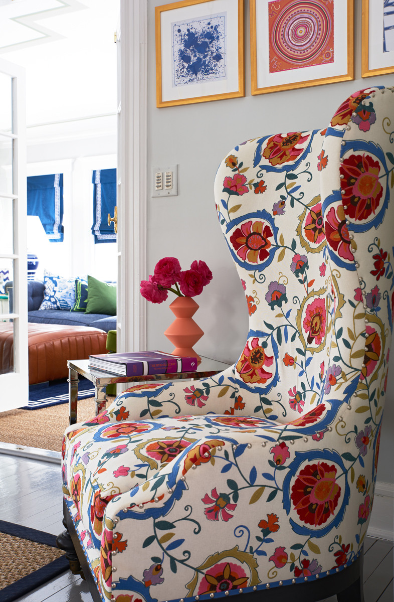 A slightly overscale wing-back chair in a botanical print sets a cheery tone in the formal living room.