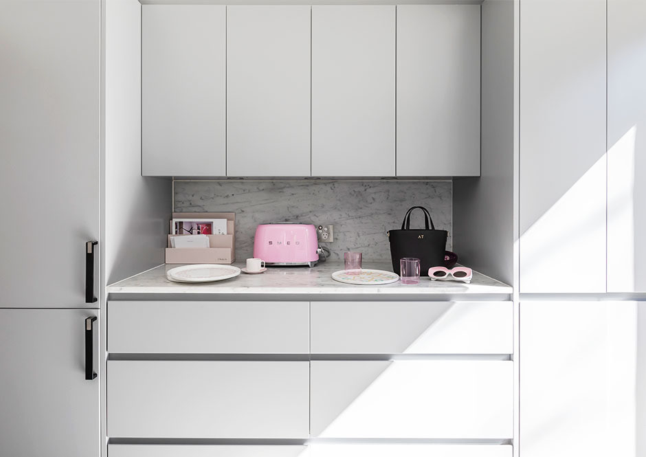 Clean lines and playful pops of pink make Tran's townhouse both accessible and stylish. SMEG Toaster | Custom Cabinetry | The Daily Edited Letter Holder | The Daily Edited Tote.