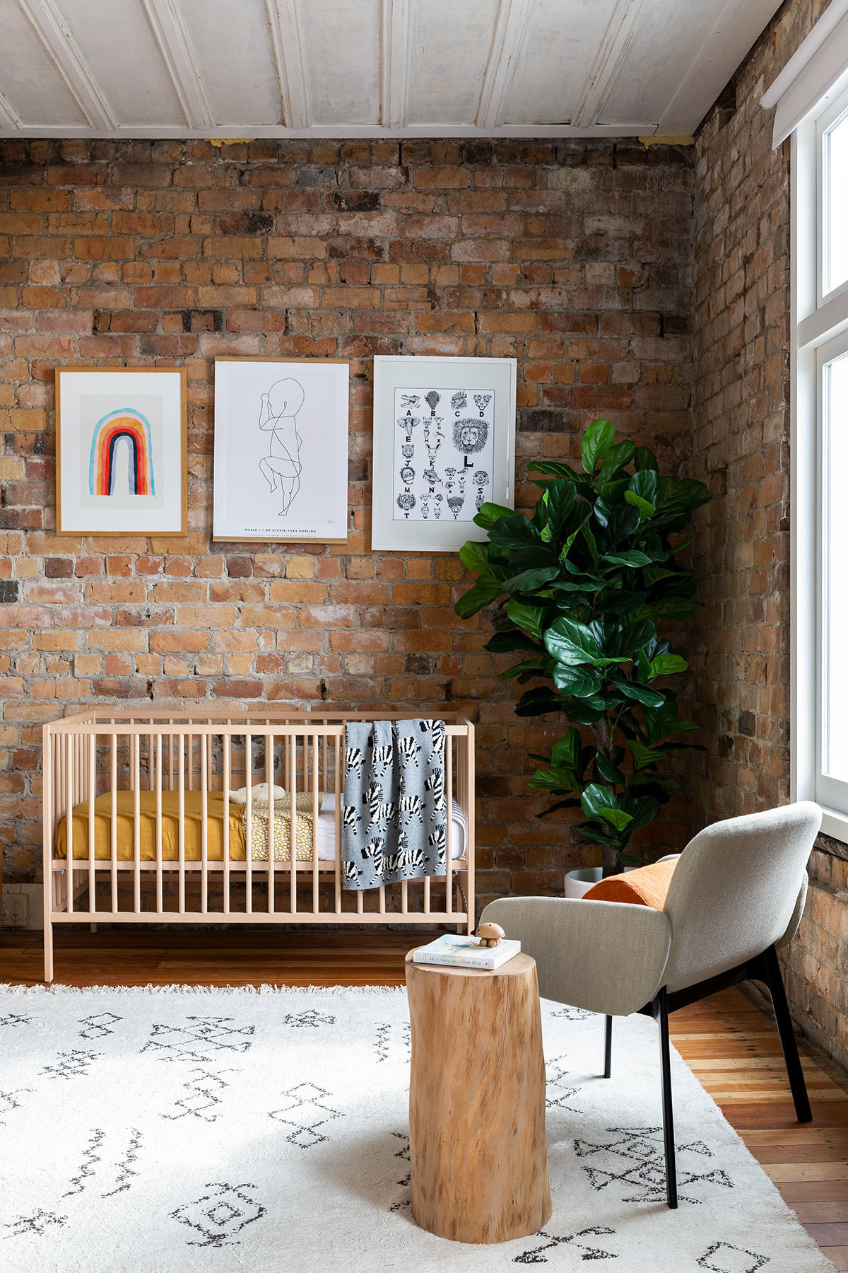 Stevie's nursery nook, complete with an IKEA crib and Città accent chair, is a calming, ultimately serene space. Nature Baby, Città Bedding; The Birth Poster Artwork; Custom Artwork; Custom Stool; Città Pillow; Flooring Direct Rug.
