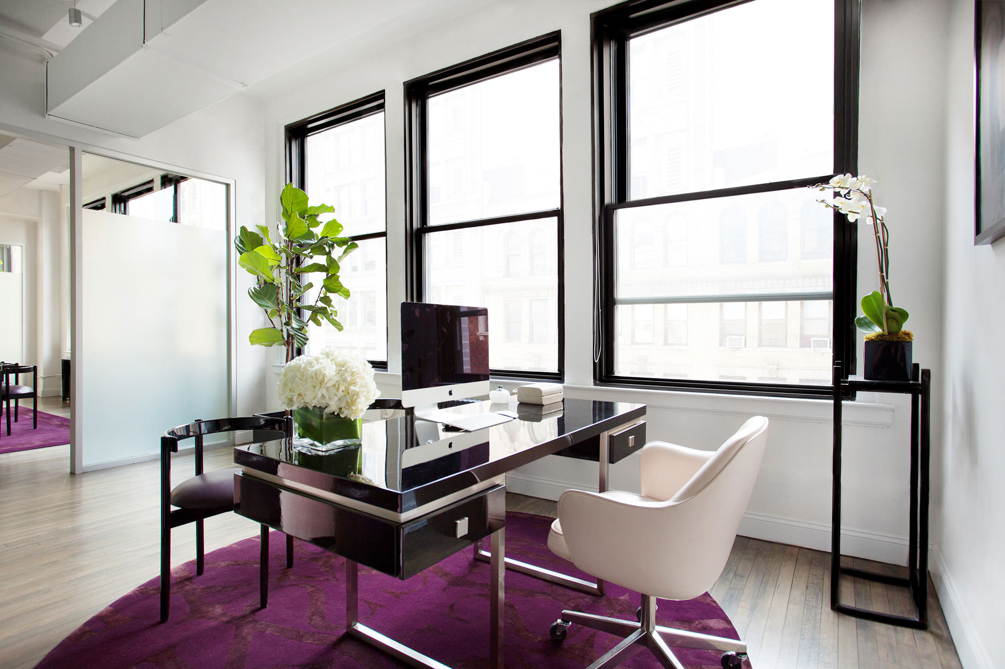 White orchids and roses add an elegant touch to the office's purple, black, and white surroundings.