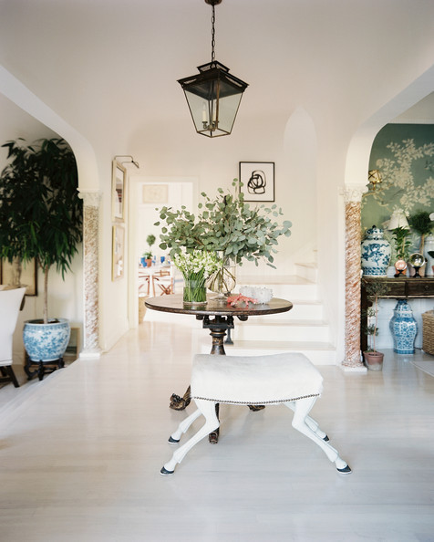 In Sikes's expansive foyer, glass vases filled with paperwhites and eucalpytus leaves adorn an antique Asian-style table paired with a tabouret chèvre.
