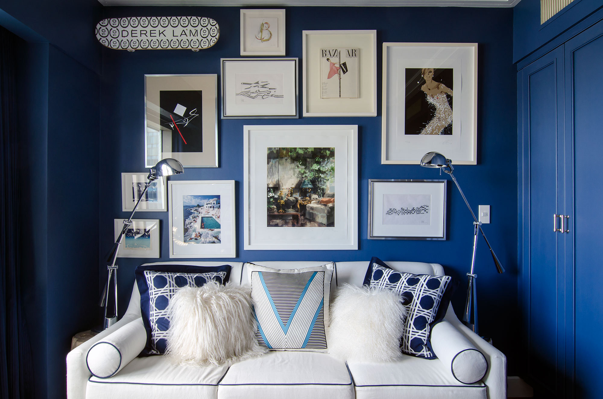 White-framed works and a pristine sofa create dramatic contrast in the indigo-hued study.