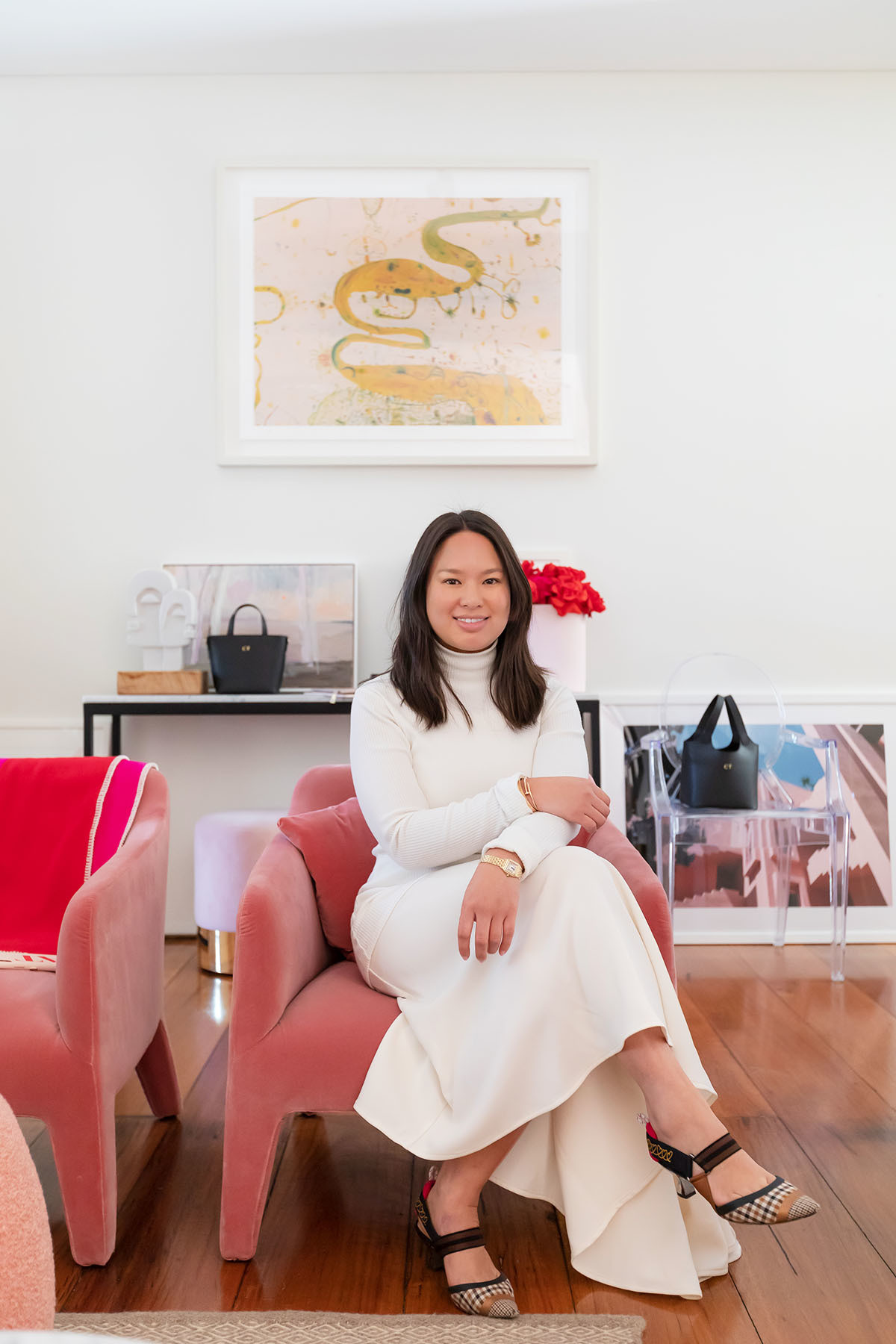 """My place is small and I needed to have that flow on space to let in more light,"" explains Tran, pictured here on a plush Jardan armchair. ""I think my home generally adheres to the Sydney vibe — it&squot;s quite conservative and is a pretty good use of a small space."""
