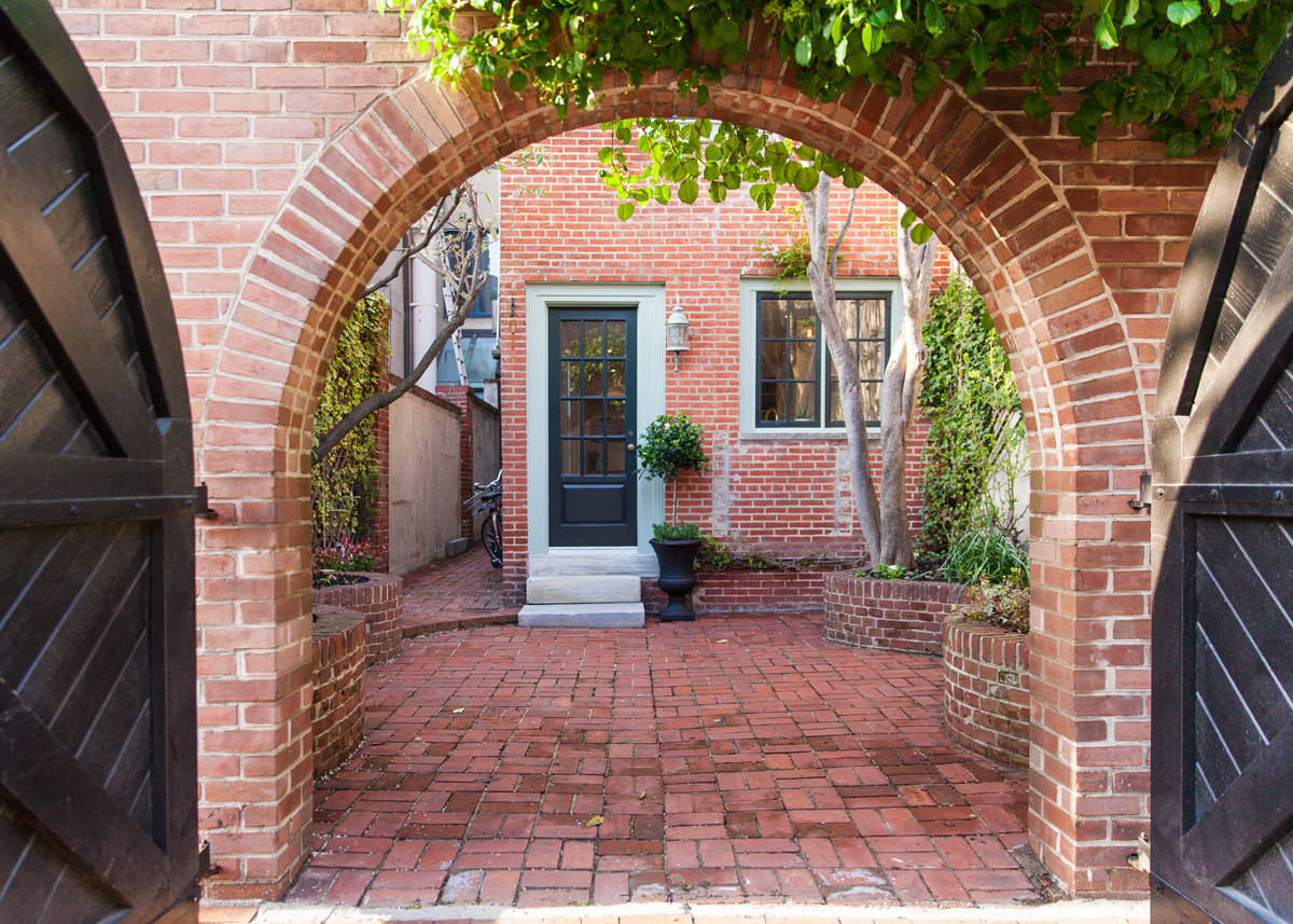 A brick-lined courtyard leads to the back entrance.