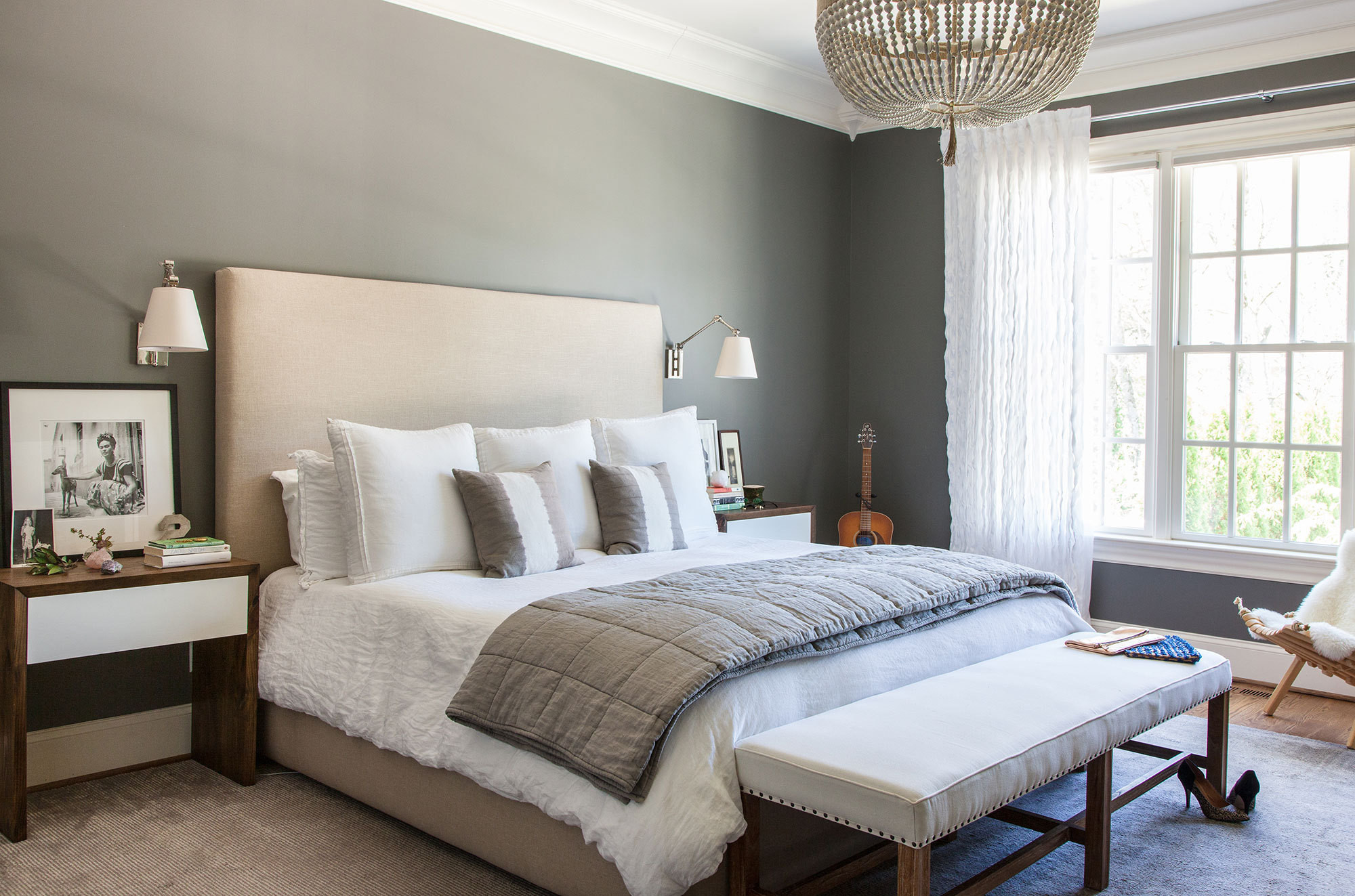 A serene master suite spotlights a beaded chandelier and a pair of bedside tables created by the designer's husband, artist and furniture designer James Wilson.
