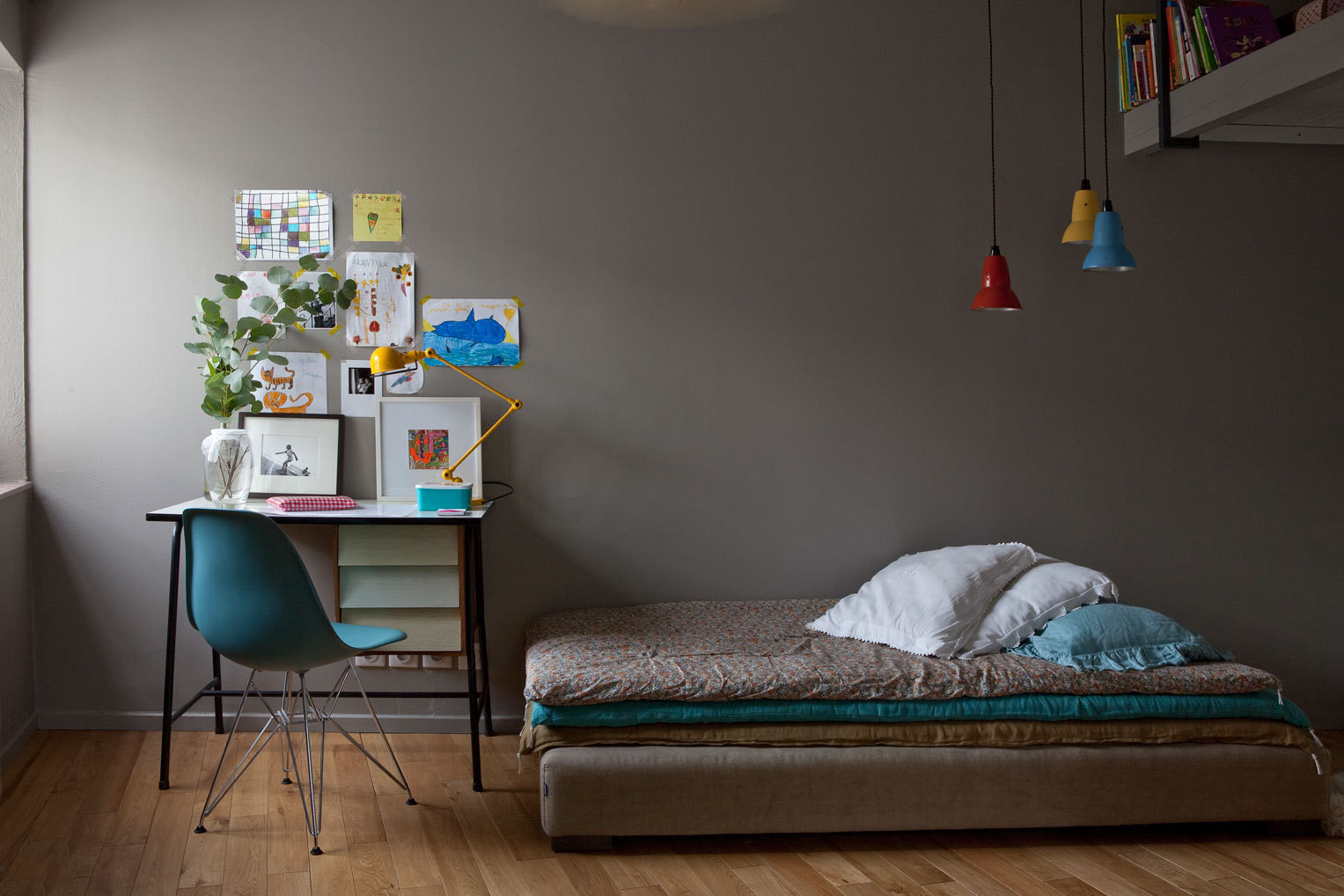 A child's room is filled with secondhand furnishings and vintage pieces in warm shades.